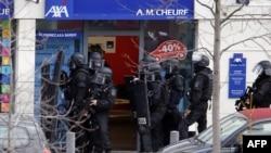 Полиция у дверей почтового отделения в пригороде Парижа Коломб, где вооруженный мужчина захватил в заложники двух человек. 16 января 2015 года.