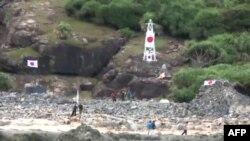 Японские националисты устанавливают флаг Японии на острове Сенкаку. 19 августа 2012 года.