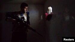 یک عضو ارتش آزاد سوریه، گروهی که از یک سو با دولت و از سوی دیگر با «حکومت اسلامی» در جنگ است