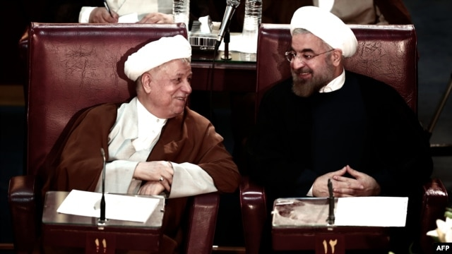 Former Iranian President Akbar Hashemi Rafsanjani (left) chats with current President Hassan Rohani during a session of the Assembly of Experts in Tehran on September 3.