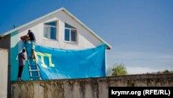 Установка крымскотатарского флага на частном доме накануне праздника Курбан-Байрам. Феодосия, село Ближнее, 13 сентября 2016. Фото Алины Смутко