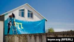 Qurban Bayramı arfesinde şahsiy evniñ üzerinde Qırımtatar bayrağı pekitile. Kefe, Bay Buğa qasabası, 13 sentâbr 2016 senesi. Alina Smutkonıñ çekken fotoresimi