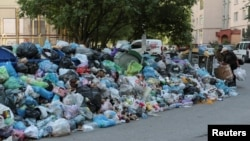 People stand next to a pile of trash in Lviv on June 19.