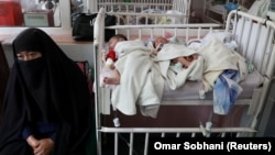 Newborn children who lost their mothers during the May 12 attack lie on a bed at a hospital in Kabul.