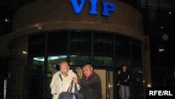 Мұхтар Әлиев (сол жақта) және оны күтіп алушы азамат Алматы әуежайынан шығып келеді. Алматы, 4 қазан 2009 жыл.
