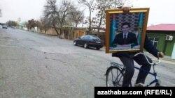 Tigirli prezident G.Berdimuhamedowyň suratyny alyp barýar, Türkmenistan
