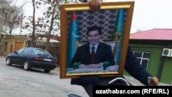 Türkmen prezidentiniň portretini tigirde göterip barýan bir oglan. Arhiwden alnan illýustrasiýa suraty.