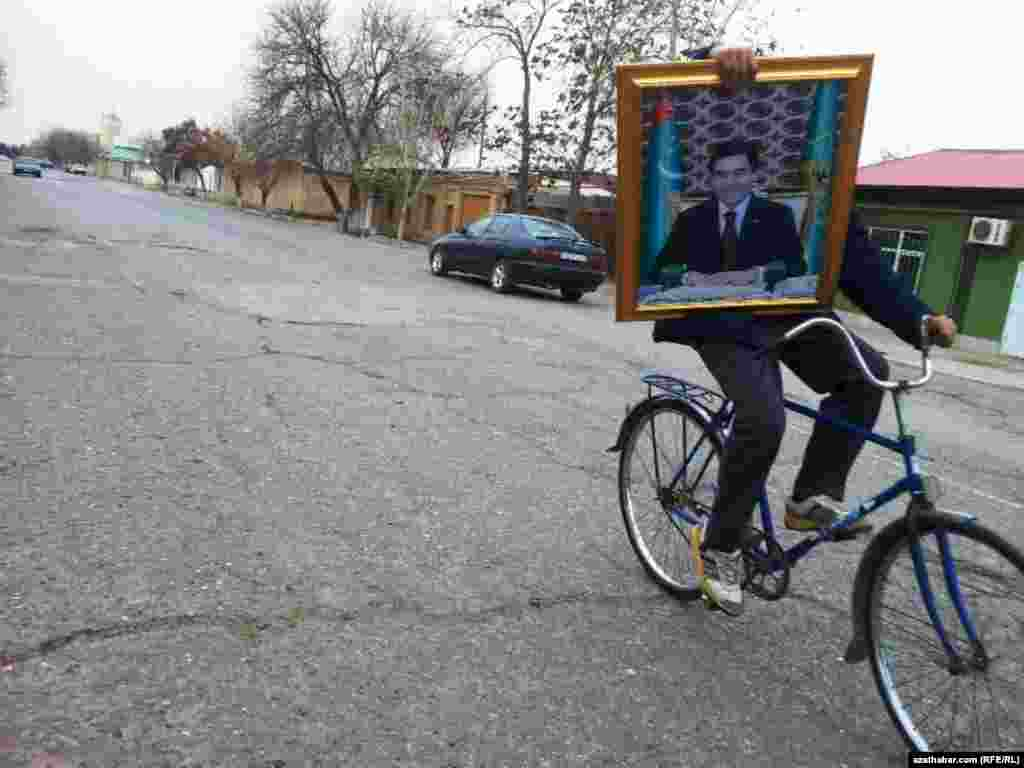 Tigirli gelyän bir oglan elinde prezident G.Berdimuhamedowyň portredini saklaýar.