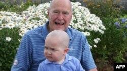 Бывший президент США Джордж Буш вместе с сыном одного из сотрудников своей охраны на коленях в Кеннебанкпорте, штат Мэн, 24 июля 2013 года