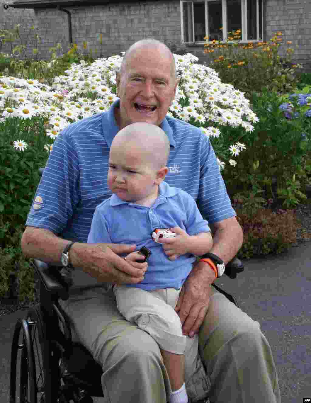 Former U.S. President George H.W. Bush poses in Maine with his head shaved to show support for 2-year-old Patrick, the son of one of Bush's security staff. His surname is being withheld at the family's request. Patrick has lost his hair from leukemia treatments. Some 26 other members of his security staff also shaved their heads. Bush and his wife, Barbara, lost a 4-year-old daughter, Robin, to leukemia nearly 60 years ago. (AFP/Office of George Bush)