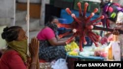 Індійський поліцейський пояснює вуличному торговцю основи безпечного дистанціювання між людьми