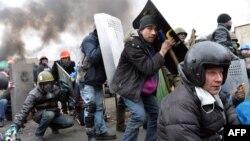 """Антиправительственные демонстранты на """"Евромайдане"""" прикрываются щитами. Киев, 20 февраля 2014 года."""