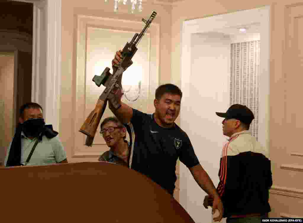 An Atambaev supporter wields a partly disassembled automatic weapon that appears to have been seized from special forces troops.