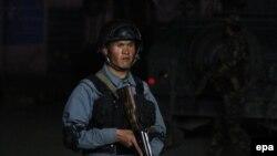 Кабулдегі содырлар басып алған қонақүй маңында тұрған қауіпсіздік қызметкері. Ауғанстан, 13 мамыр 2015 жыл.