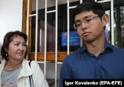 Raisa Atambaeva and her son Kadyr wait outside the State Committee for National Security in Bishkek on August 16.