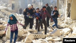People and a civil-defense worker carry children at a damaged site after an air strike on rebel-held Idlib on March 19.