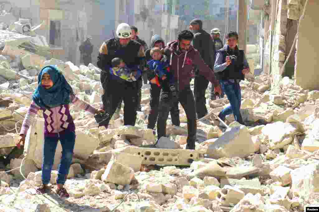 Civilians and rescue workers carry children at a damaged site following an air strike on the rebel-held city of Idlib in Syria. (Reuters/Ammar Abdullah)