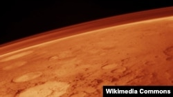 Space -- The tenuous atmosphere of Mars, visible on the horizon in this low-orbit photo, undated