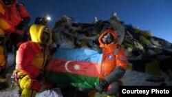 Участники экспедиции с развернутым азербайджанским флагом на вершине Эвереста. Справа - Мурад Ашурлы. Участок вершины за спиной альпинистов покрыт флагами и вымпелами. 19 мая 2013
