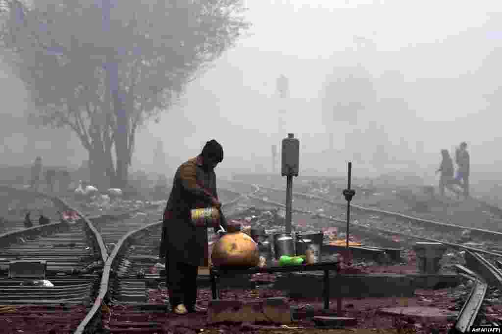 A man fills a pot with milk on a railway track during a cold and foggy morning in Lahore,Pakistan, on January 8. (AFP/Arif Ali)