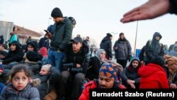 Migrants sit at the Serbian-Hungarian border as they protest to demand passage to the European Union, near Kelebija, Serbia, on February 6.