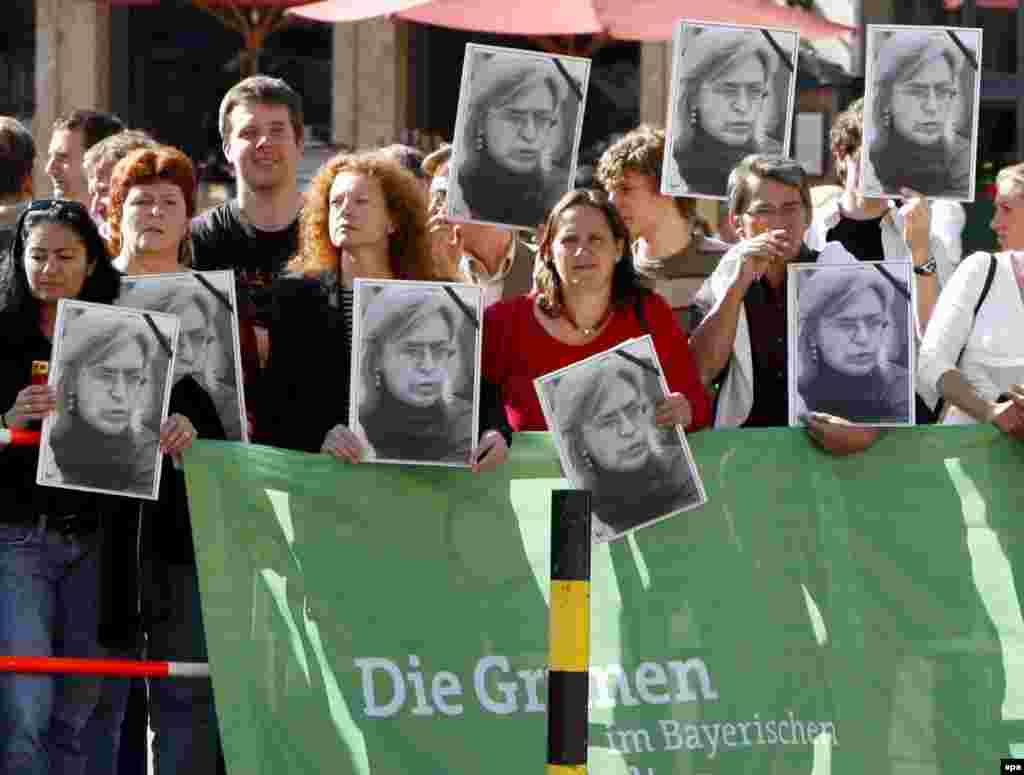"Germany -- Members of the Bavarian Green Party demonstrate with photos of the recently killed Russian journalist Anna Politkovskaya during the visit of Russian President Vladimir Putin in Munich, 11Oct2006 - 11 üktäber könne Germaniäneñ Münxen şähärenä kilgäç Putinnı Politkovskaya räsemnären totqan keşelär qarşı aldı. Ber kön aldan Putin anıñ ""Rusiädäge säyäsi tormışqa yoğıntısı yuq ide"" digän süzläre belän küplärneñ açuın çığarğan ide. (epa)"
