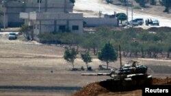 Неизвестные бойцы стоят на посту в сирийском городе Кобани, около пересечения турецко-сирийской границы в юго-восточной части города Суруч в провинции Шанлыурфа, 8 октября 2014 года.