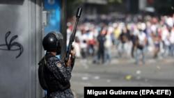 Pripadnik policije tokom nemira na ulicama Karakasa, januar 2019.