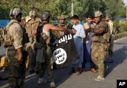 A member of the former Afghan government's security forces holds the Islamic State group's flag after an attack in Jalalabad in August 2020.