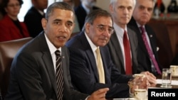U.S. President Barack Obama (left) is flanked by Defense Secretary Leon Panetta as he speaks at a Cabinet meeting in Washington in late January.