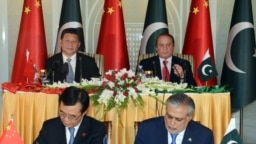 Pakistan -- Chinese President Xi Jinping (top-L) and Pakistani Prime Minister Nawaz Sharif (top-R) look on as Pakistani Finance Minister Ishaq Dar (R) and a Chinese official (L) sign an MoU at Prime Minister's House in Islamabad. Chinese President Xi Jinp