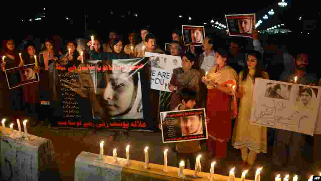 Civil society activists and journalists in Islamabad carry candles during continuing protests against the assassination attempt.