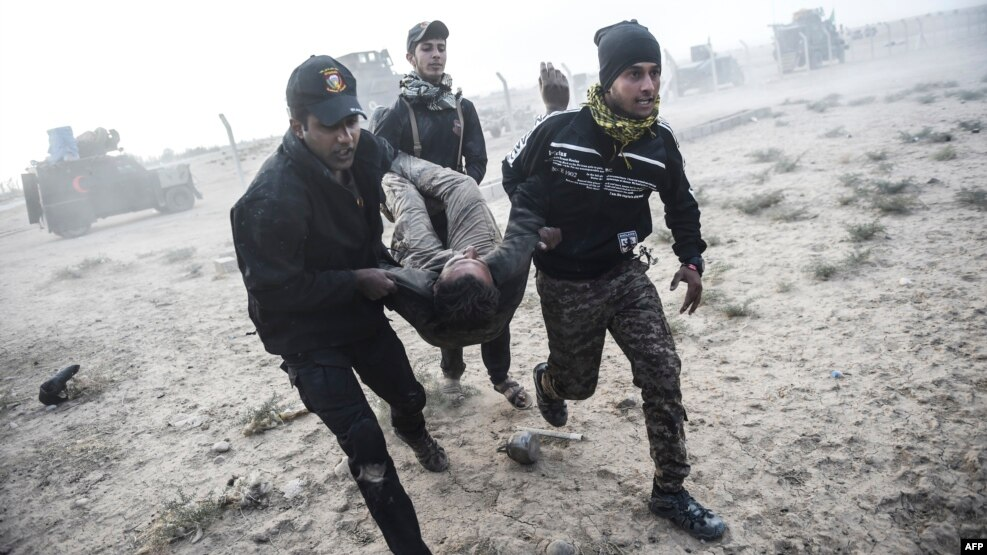 Iraqi counterterrorism troops carry an injured comrade during clashes with Islamic State militants near the village of Bazwaya, on the eastern edge of Mosul, on October 31.