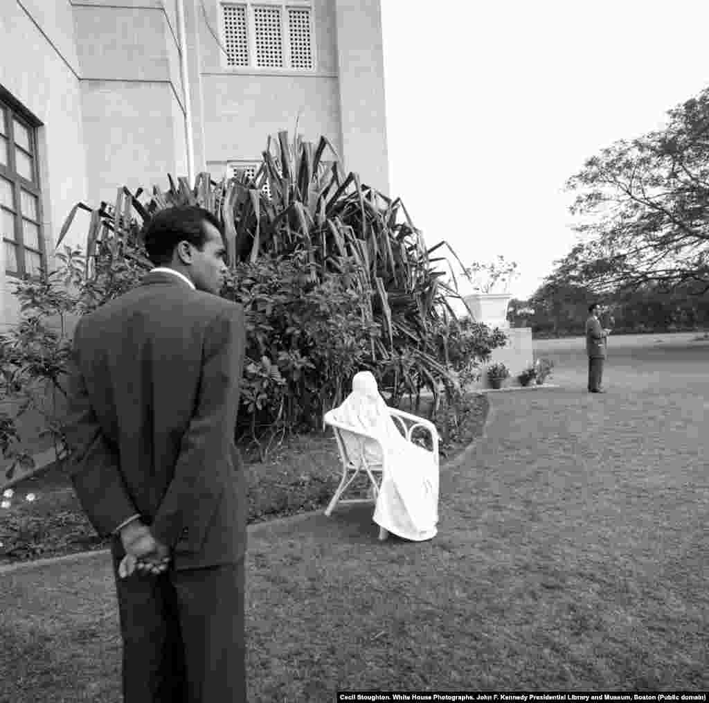 Allah Rakkhi, the wife of Bashir Ahmad, sits in a chair on the grounds of President Khan's residence in Karachi, where the camel ride took place.