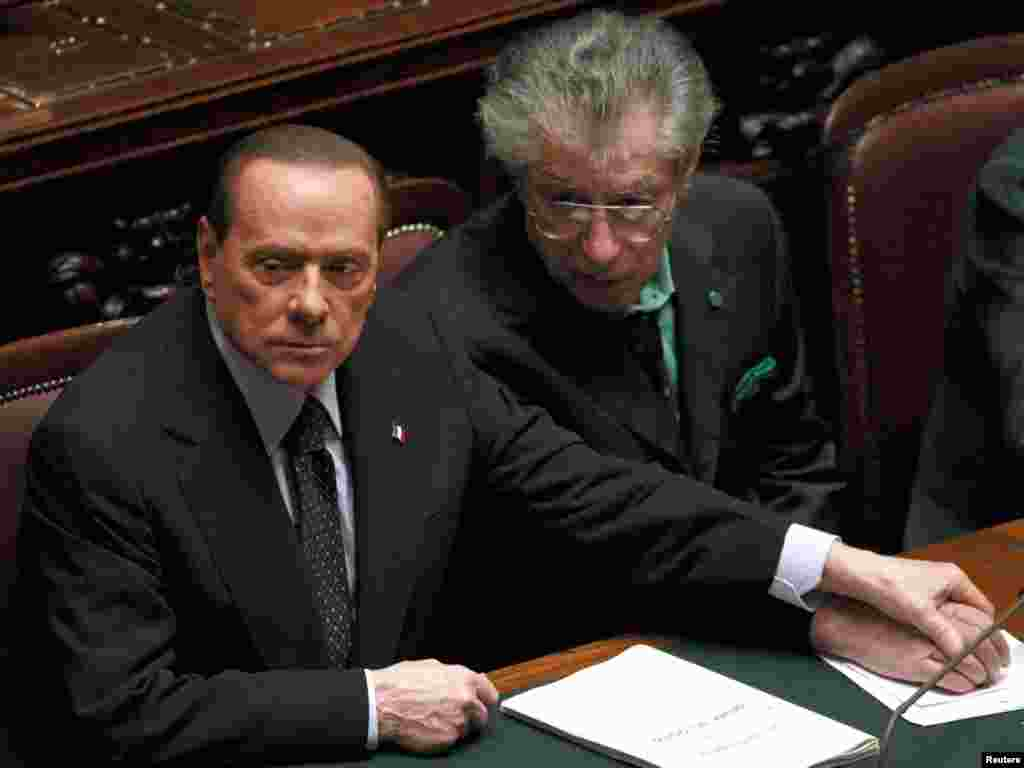 Italian Prime Minister Silvio Berlusconi (left) holds League North Party leader Umberto Bossi's hand during a finance vote. Berlusconi has pledged to stand down onced parliament passes budget reforms. (Photo for Reuters by Tony Gentile)