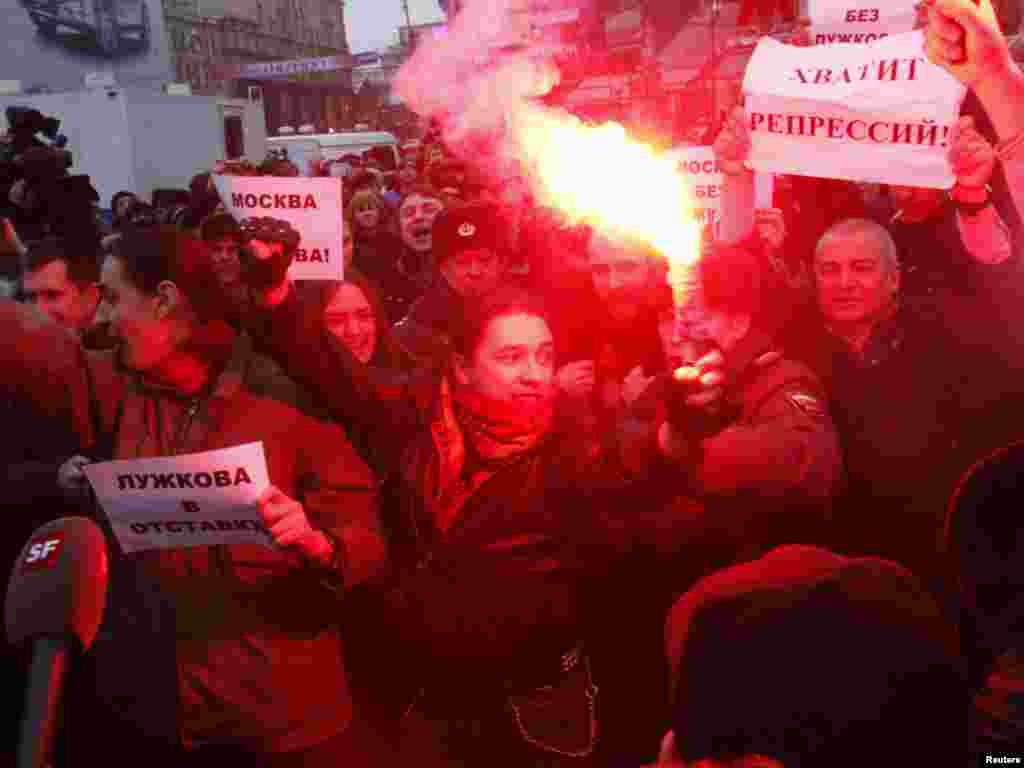 Opposition supporters light flares and shout slogans at an unsanctioned rally in Moscow.