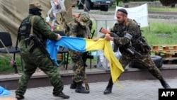 Проросійські бойовики з батьйону «Восток» розривають український прапор, Донецьк, 29 травня 2014 року
