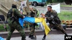 """""""Чыгыш"""" деген орусиячыл батальондун аскерлери Донецктеги өкмөттүк имарат алдында украин желегин айрып жатышат, 29-май, 2014"""