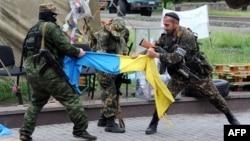 Бойовики угруповання «ДНР», яке в Україні офіційно визнане терористичним, шматують прапор України. Донецьк, 29 травня 2014 року