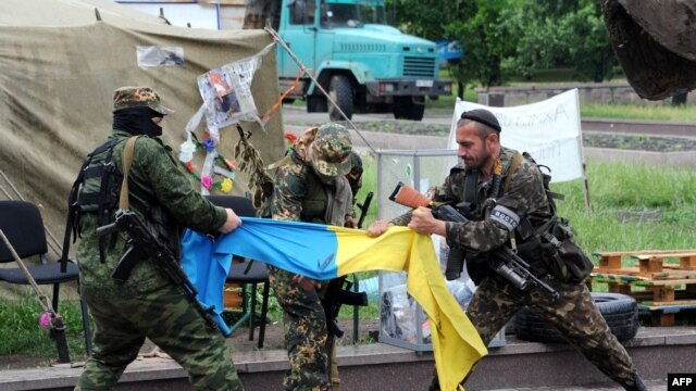 Pro-Russian fighters of the Vostok (East) Battalion rip apart a Ukrainian flag outside the regional administration building in the eastern city of Donetsk, on May 29.