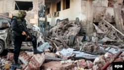 Egyptian security forces inspect the site of a deadly explosion outside police headquarters in Mansoura, Egypt, in December 2013. The Sinai-based militant group Ansar Bayit al-Maqdis had threatened the country's soldiers with death unless they deserted the army.