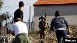 Pamje e mëhershme ku shihet një ushtar izraelit me armë para tre palestinezëve në Bregun Perëndimor