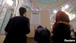 Иранские избиратели рассматривают список кандидатов в Совет экспертов на избирательном участке в Тегеране. 26 февраля 2016 года.