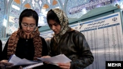 Two Iranian women cast ballots at a polling station in Tehran in Iran's city council elections in 2006.