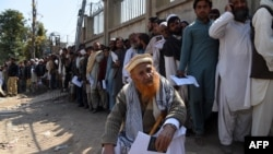 Afghan nationals carry their passports as they wait to extend their visas outside the Pakistani immigration office in Peshawar. (file photo)