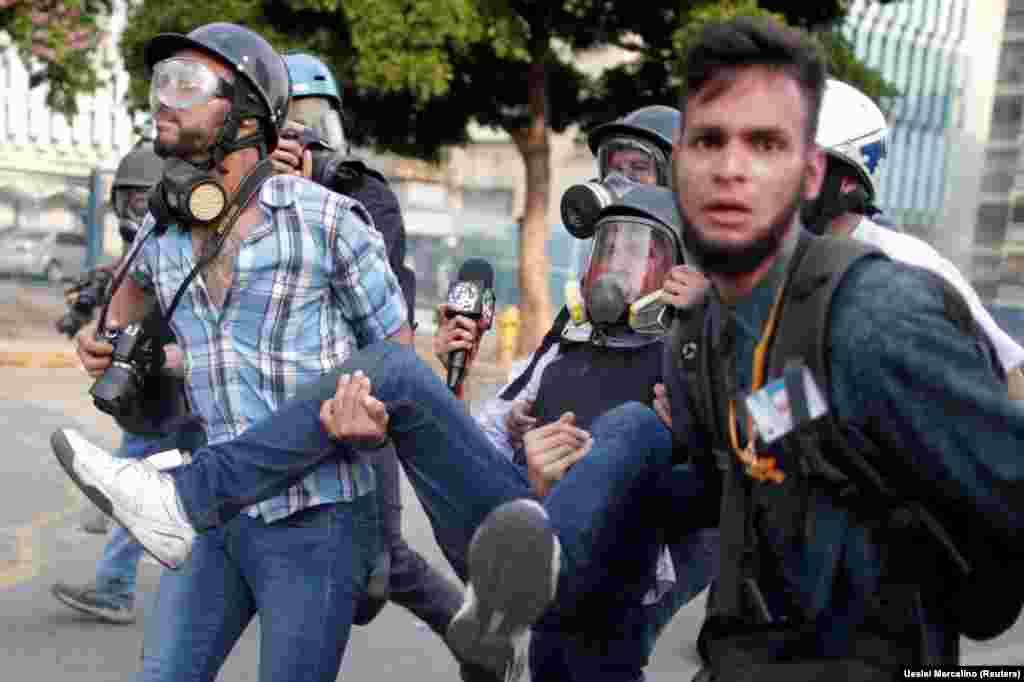 An injured reporter is carried away during a rally against the government of Venezuela's President Nicolas Maduro in Caracas on May 1. (Reuters/Ueslei Marcelino)