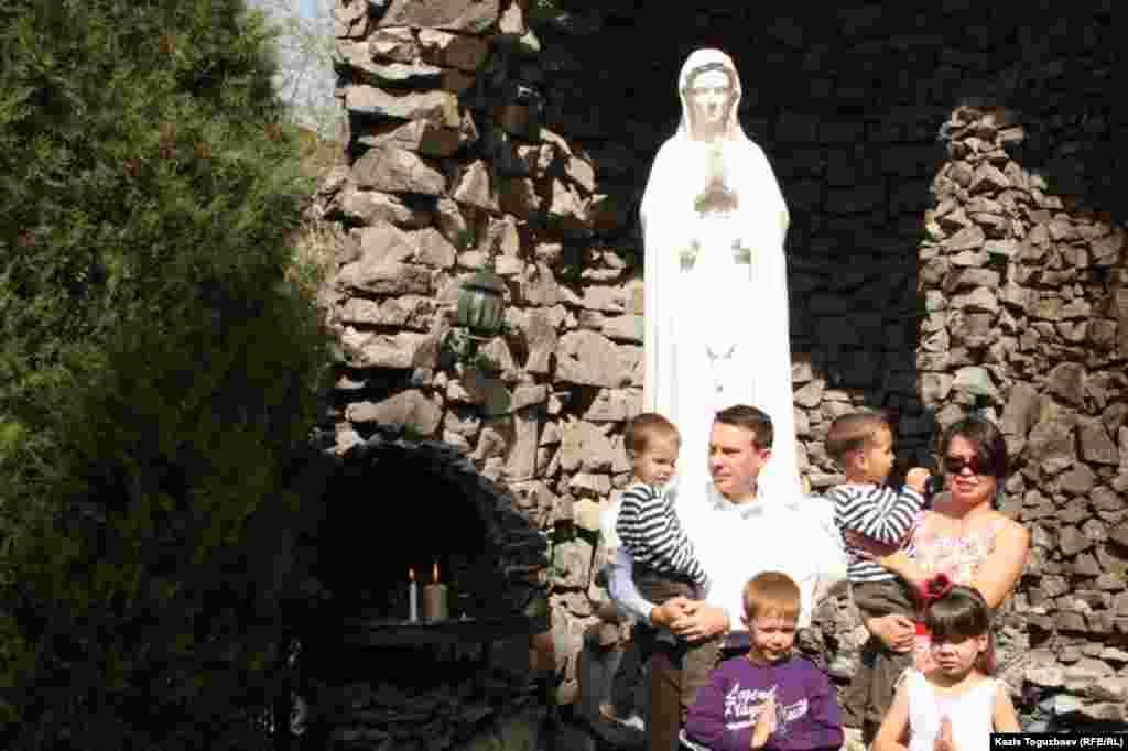 Супруги Асем и Марек Стэч с детьми у статуи Девы Марии. Алматы, 31 марта 2013 года.