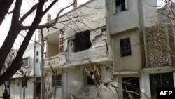 Ndërtesë e dëmtuar nga luftimet në një lagje të Homsit