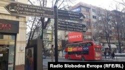 Тројазична патоказна табла ( на македонски, англиски и албански) во центарот на Скопје.