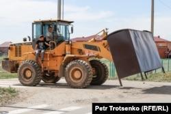Трактор устанавливает автобусную остановку в селе Кызылсуат. Акмолинская область, 10 июня 2020 года.
